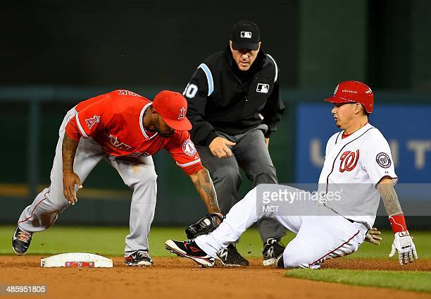 Washington Nationals catcher Jose Lobaton is tagged out at second base by Los Angeles Angels second baseman Howie Kendrick trying to stretch a single...