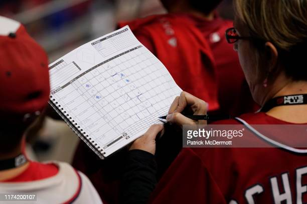 Washington Nationals fan keeps track of the game in a score book in the seventh inning during Game 3 of the NLDS against the Los Angeles Dodgers at...