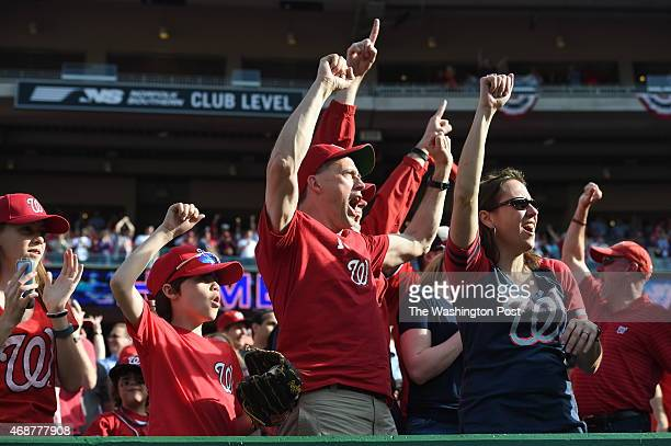 Washington Nationals fans including John Dowd of Washington and his son JP Dowd celebrate Bryce Harper's fourth inning home run against the New York...