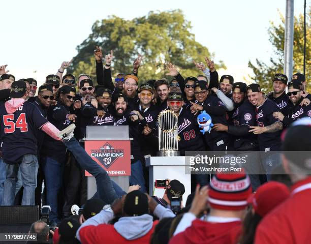 Washington Nationals first baseman Ryan Zimmerman lays on the stage as he takes a team photo during the rally to honor their 2019 World Series...