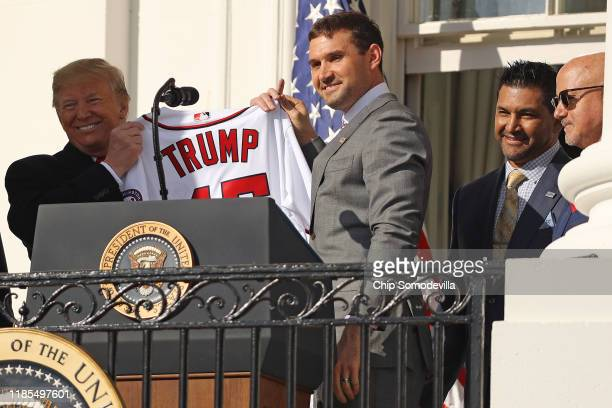Washington Nationals first baseman Ryan Zimmerman presents US President Donald Trump with a team jersey during a celebration of the 2019 World Series...