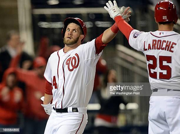 Washington Nationals left fielder Bryce Harper high fives Washington Nationals first baseman Adam LaRoche after scoring on a single by Washington...