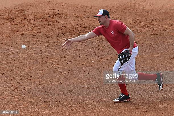 Washington Nationals left fielder Ryan Zimmerman tosses the ball back towards first while taking grounders as a first baseman during spring training...