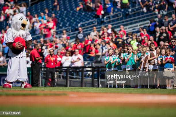 Washington Nationals mascot Screech stands near Girl Scout troops during the National Anthem before the game between the Washington Nationals and the...