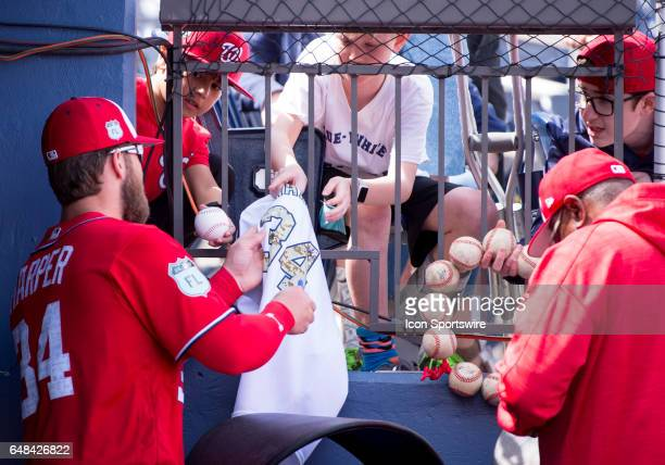 Washington Nationals Outfielder Bryce Harper and Washington National Manager Dusty Baker sign autographs for fans in the dugout during a MLB spring...