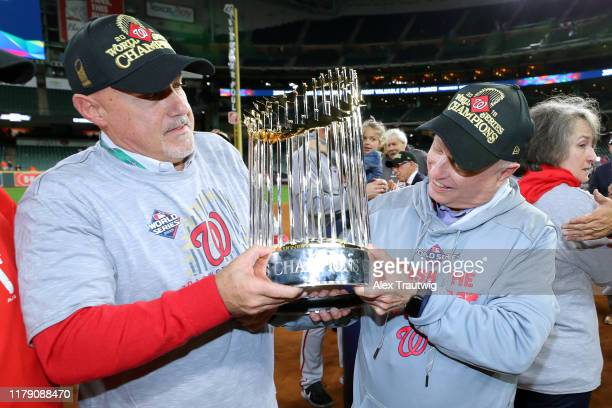 Washington Nationals owner Mark Lerner and general manager Mike Rizzo hold the World Series trophy after the Nationals defeat the Houston Astros in...
