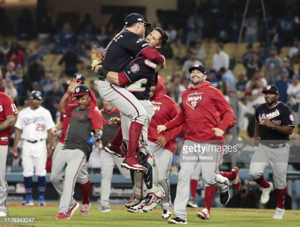 Washington Nationals pitcher Sean Doolittle and catcher Yan Gomes celebrate after beating the Los Angeles Dodgers in Game 5 of the National League...