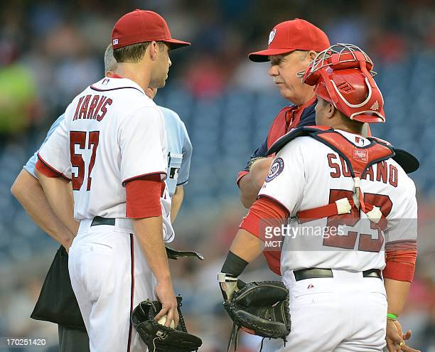 Washington Nationals pitching coach Steve McCatty back right has a word with Washington Nationals starting pitcher Nathan Karns during a rough second...