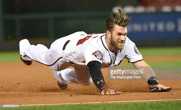 Washington Nationals right fielder Bryce Harper dives into third base on a single by Jayson Werth during sixth inning action on September 17 2015 in...