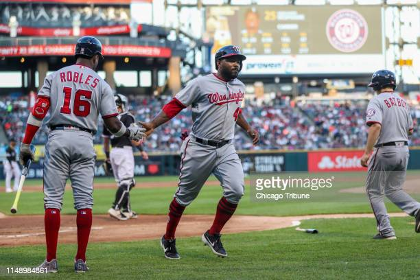 Washington Nationals second baseman Howie Kendrick celebrates with Washington Nationals center fielder Victor Robles after scoring off a sacrifice...