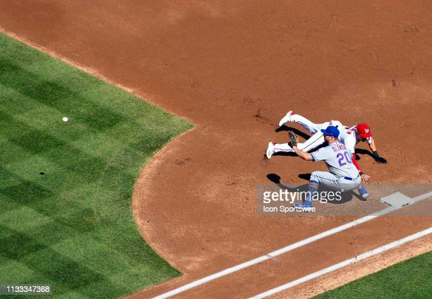 Washington Nationals shortstop Trea Turner dives back into first base ahead of the throw to New York Mets first baseman Pete Alonso during the...