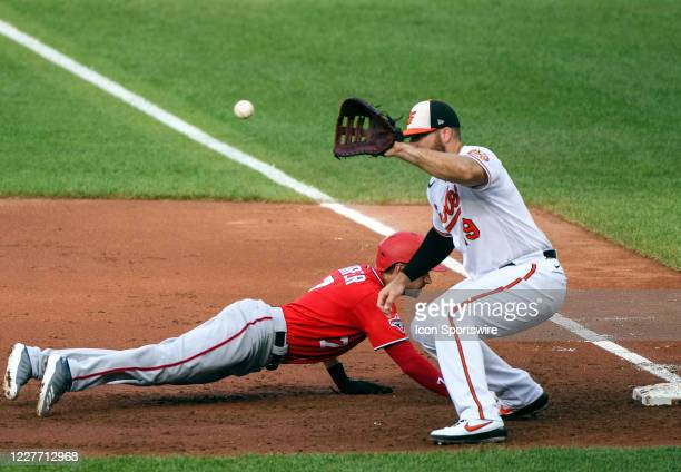 Washington Nationals shortstop Trea Turner dives back into first base as the throw comes to Baltimore Orioles first baseman Chris Davis during a...