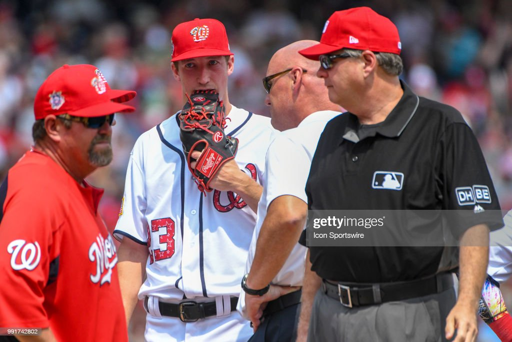 Washington Nationals starting pitcher Erick Fedde (23) comes out of the game after a second inning injury as umpire Jerry Layne (24) confers with Nationals pitching coach Derek Lilliquist (38) during the game between the Boston Red Sox and the Washington Nationals on July 4, 2018, at Nationals Park, in Washington D.C. The Boston Red Sox defeated the Washington Nationals, 3-0 to sweep the series.