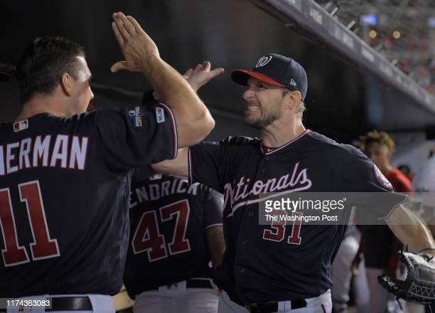 Washington Nationals starting pitcher Max Scherzer right high fives Washington Nationals first baseman Ryan Zimmerman after finishing the 7th inning...