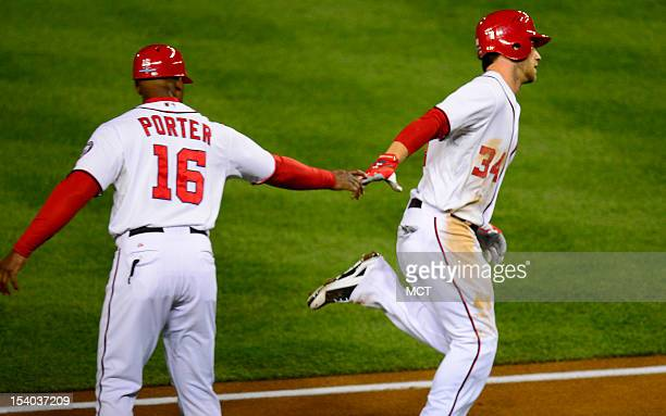 Washington Nationals third base coach Bo Porter congratulates Washington Nationals center fielder Bryce Harper on his solo homer against the St Louis...