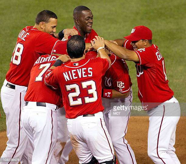 Washington Nationals third baseman Ryan Zimmerman is mobbed by teammates at first base after hitting a sacrafice fly to score the game-winning run...