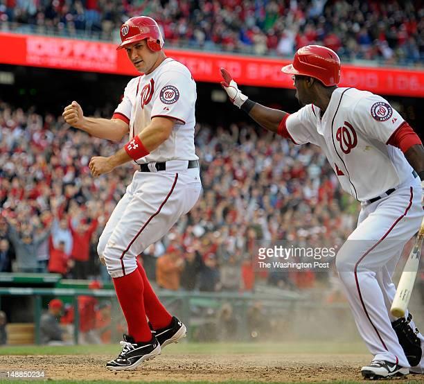 Washington Nationals third baseman Ryan Zimmerman left celebrates after scoring the game winning run on a wild pitch in the 10th inning Teammate...
