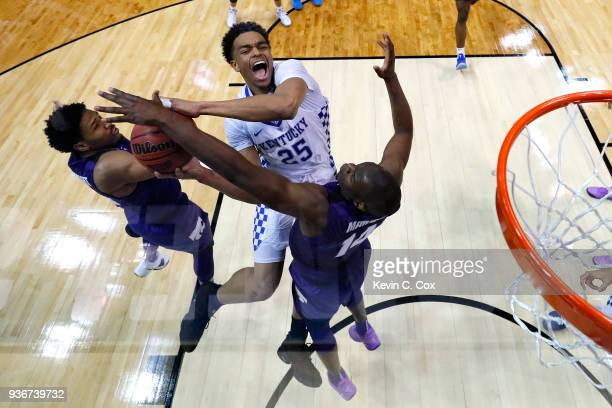 Washington of the Kentucky Wildcats goes up with the ball against Amaad Wainright and Makol Mawien of the Kansas State Wildcats in the second half...