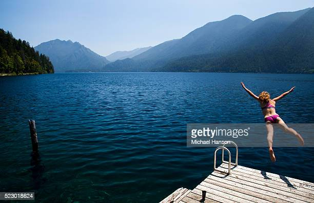 usa, washington, olympic national park, woman jumping to lake - olympic park stock pictures, royalty-free photos & images
