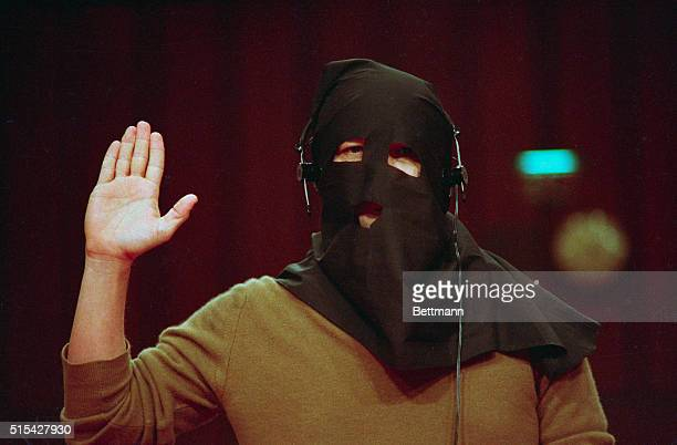 Pilot Floyd Carlton wearing a hood provided by the witness protection program is sworn in prior to testimony on Panamanian General Manuel Noriega...