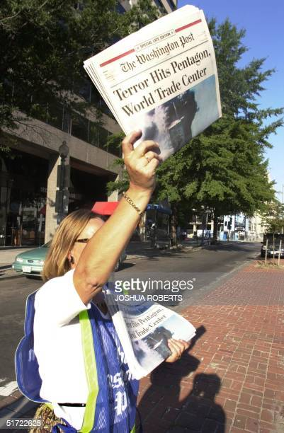 Washington Post employee holds copies of a special edition of the newspaper for sale 11 September in Washington, DC. The paper put out a special...