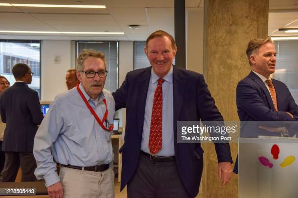 Washington Post employees, alumni, and guests - including columnist Robert J. Samuelson, L, and former publisher Don Graham - gather for a ribbon...