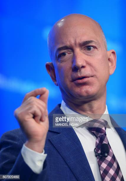 Washington Post owner Jeff Bezos gestures as he speaks during the inauguration of the Washington Post Headquarters on January 28 2016 in Washington...