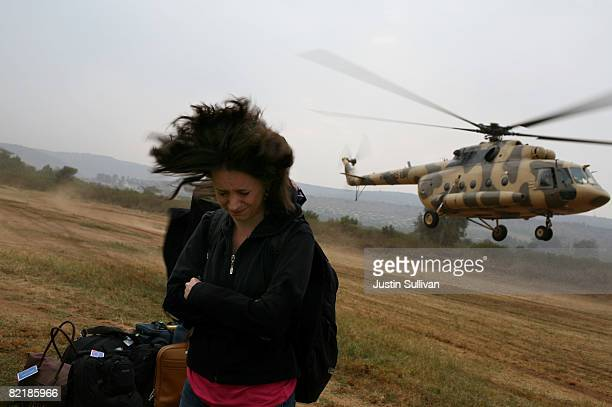 Washington Post reporter Anne Kornblut shields herself from a helicopter's rotor wash as she accompanies former US President Bill Clinton on a tour...