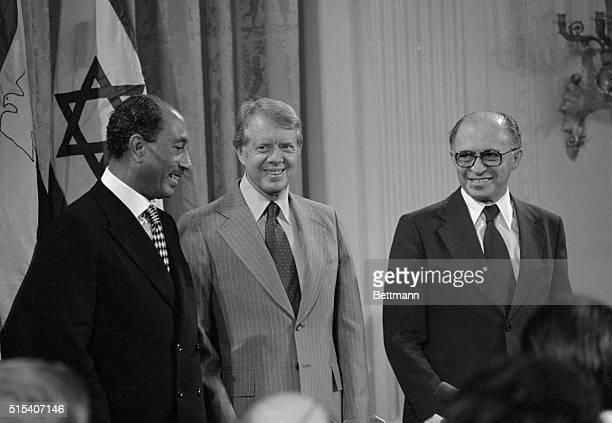 President Carter is flanked by Egyptian President Anwar Sadat and Israeli Prime Minister Menachem Begin in the East Room of the White House where the...