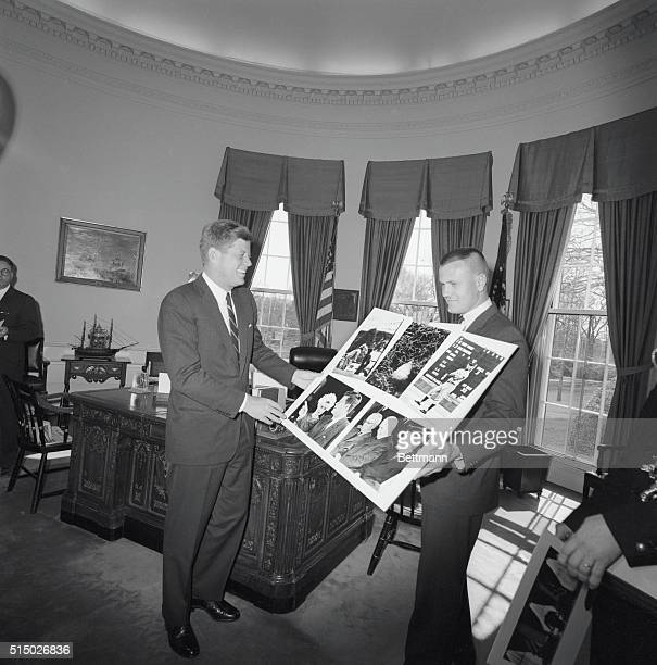 President Kennedy gets a preview of United Press International photographer James Atherton's picture portfolio that won first prize in the annual...
