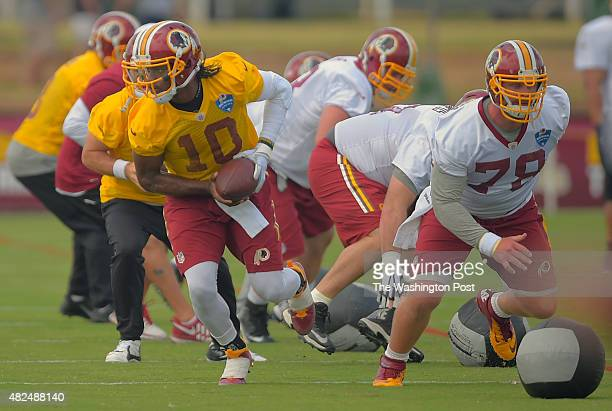 Washington quarterback Robert Griffin III left takes a snap from center Kory Lichtensteiger right during day 1 of the Washington Redskins training...