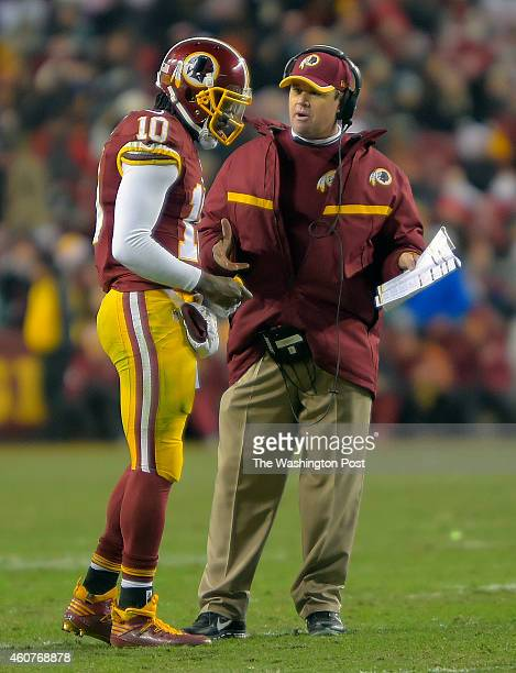 Washington quarterback Robert Griffin III left talks with head coach Jay Gruden during a 4th quarter time out as the Washington Redskins defeated the...