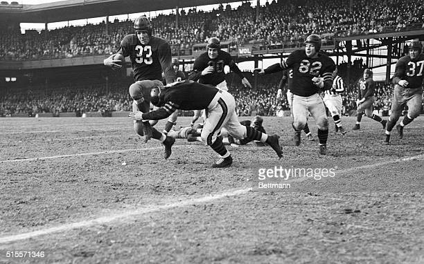 Washington Redskin football player Sammy Baugh tackled by Chicago Bear fullback Will Osmanski just before the first down of the third quarter of the...