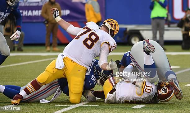 Washington Redskins center Kory Lichtensteiger has his leg bent back by New York Giants defensive end Jason PierrePaul as quarterback Robert Griffin...