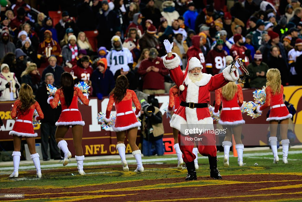 Washington Redskins cheerleaders perform as a man dressed as Santa Claus waves during the Redskins and Philadelphia Eagles game at FedExField on December 20, 2014 in Landover, Maryland.