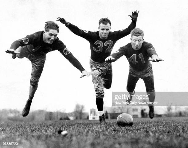 Washington Redskins Ed Justice Bob McChesney and Henry Krause lunge for the football during practice