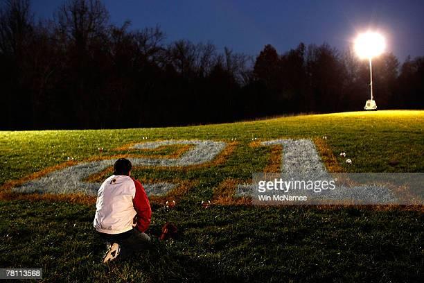 Washington Redskins fan Timothy McLeod kneels before Sean Taylor's number 21 at a makeshift memorial for the slain football player at Redskins Park...