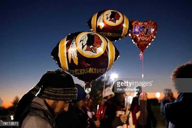 Washington Redskins fans gather at a makeshift memorial for Redskins safety Sean Taylor during a vigil at Redskins Park November 27 2007 in Ashburn...