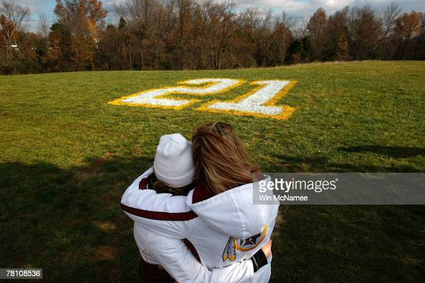 Washington Redskins fans Natalie Ragnati and Amy Goldsmith embrace in front of Sean Taylor's number 21 painted onto a field at Redskins Park November...