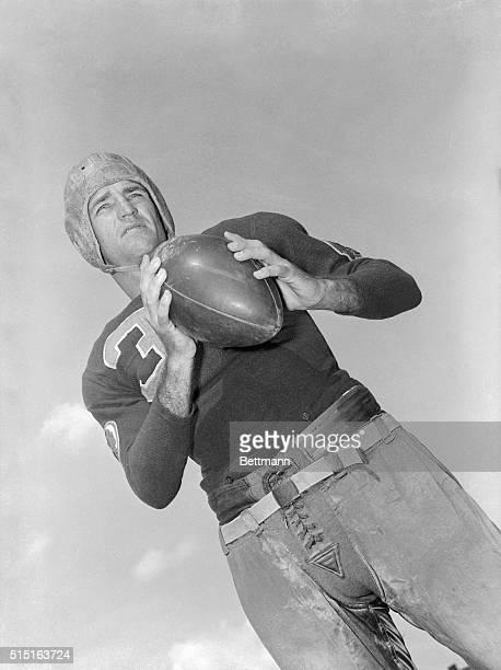 Washington Redskins' halfback, Sammy Baugh holding a football.