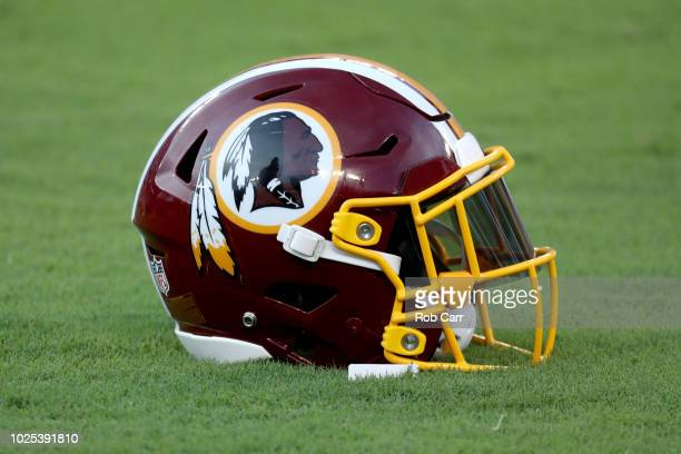 Washington Redskins helmet sits on the grass before the start of the Redskins and Baltimore Ravens preseason game at MT Bank Stadium on August 30...