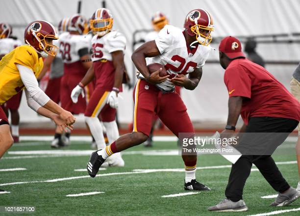 Washington Redskins newest acquisition Adrian Peterson gets the handoff from quarterback Alex Smith during his first practice with the team August 21...