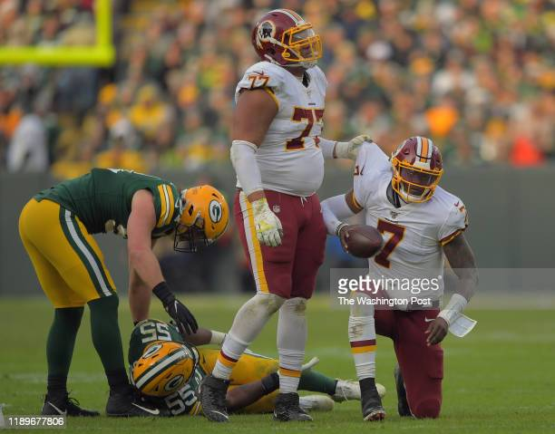 Washington Redskins offensive guard Ereck Flowers helps up Washington Redskins quarterback Dwayne Haskins after he was brought down by Packers...