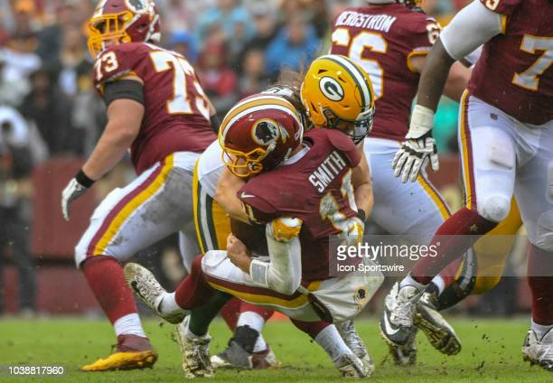 Washington Redskins quarterback Alex Smith is tackled by Green Bay Packers linebacker Clay Matthews who was called for roughing the passer in the...