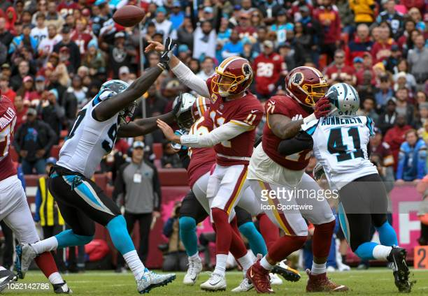Washington Redskins quarterback Alex Smith makes a pass in the first half under pressure by Carolina Panthers defensive end Julius Peppers on October...