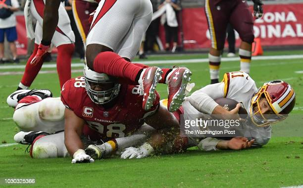 Washington Redskins quarterback Alex Smith slides and is tackled by Arizona Cardinals defensive tackle Corey Peters as he rushes for yardage late...