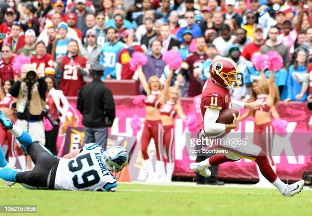 Washington Redskins quarterback Alex Smith starts to go to the turf after Carolina Panthers linebacker Luke Kuechly in action on October 14 at FedEx...