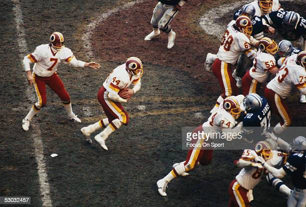 Washington Redskins' quarterback Joe Theismann runs with the ball against the Dallas Cowboys during a game at RFK stadium circa 1982 in Washington DC