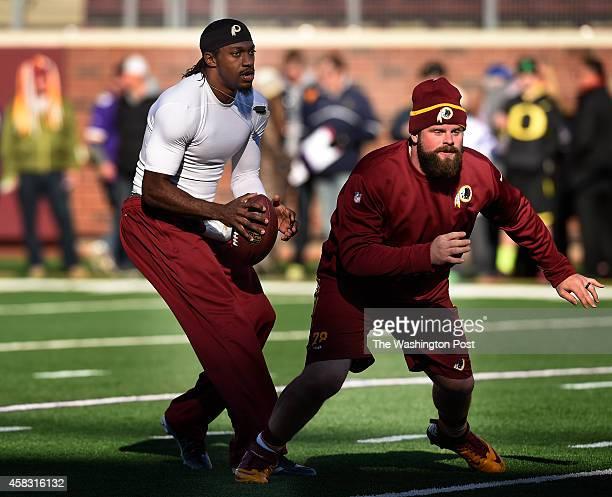 Washington Redskins quarterback Robert Griffin III drops back after taking a snap from Washington Redskins center Kory Lichtensteiger while warming...