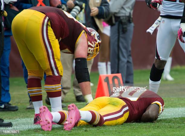 Washington Redskins quarterback Robert Griffin III lies on the grounds as teammate Kory Lichtensteiger checks on him after being tackled and injured...